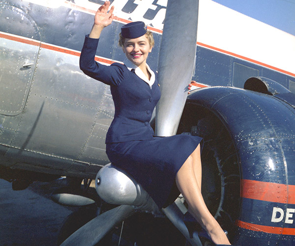 Delta stewardess sitting on DC-3 propeller waving. Wearing 1957-59 Winter Uniform.